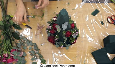 Florist decorates bouquet by greens and beautiful natural flowers.
