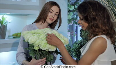 Florist demonstrates bouquet of roses
