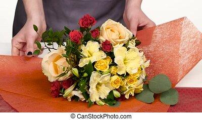 Florist does a wrap for bouquet flowers. White. Close up