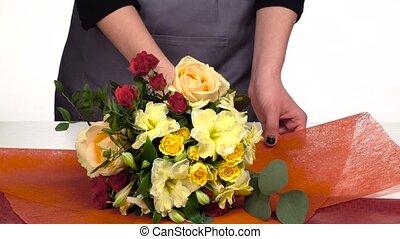Florist does a wrap for bouquet flowers. White. Slow motion. Close up