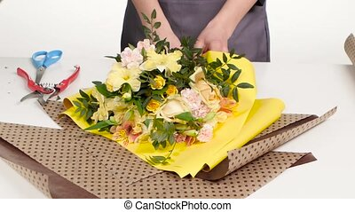 Florist does wrapping paper around bouquet. White. Close up