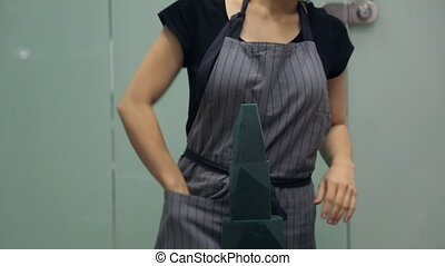 Florist during a phone call cuts the cone shape of floral sponge