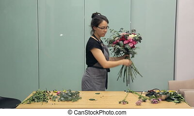 Florist finishes creation of beautiful bouquet. She works...