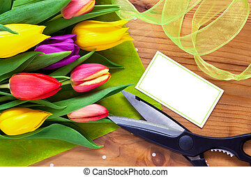 Bouquet of flowers on a table in a florist shop, blank card with copy space to add your own message.