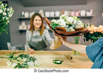 Florist gives fresh bouquet to female customer