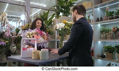 Florist giving ready floral creation to client - Cheerful...