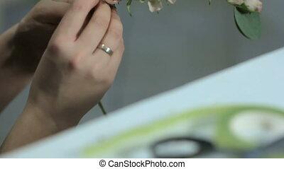 Florist hand makes crown cuts ribbon, close-up