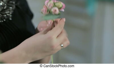 Florist hand makes crown of roses, close-up