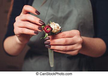 Florist hands creating flower decoration closeup.