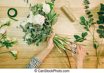 Florist hands cuts flower composition with pruner