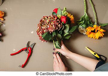 Florist hands cutting rose with garden scissors