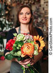 Florist hands holding bouquet flowers closeup.