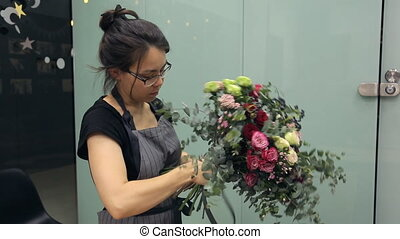 Florist hardly ties up ready beautiful bouquet with black satin ribbon