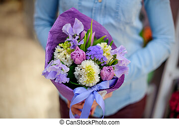 Florist holding a beautiful and cute purple bouquet of flowers