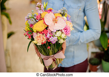 Florist holding a beautiful colorful bouquet of flowers with a cute bow