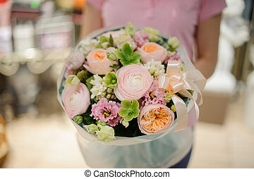 Florist holding a flower composition in soft tones consisting of roses, ranunculus and other beautiful flowers decorated with a ribbon
