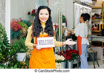 Florist holding welcome sign