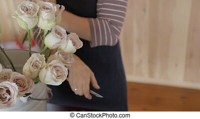 Florist in apron cuts off roses with knife and puts it in...