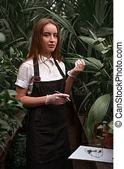 Florist in apron holds clipboard in hands