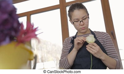 Florist in glasses clears white rose from dry petals at...