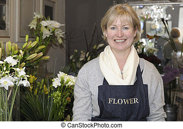 Florist in her shop surrounded by flowers smiling at camera