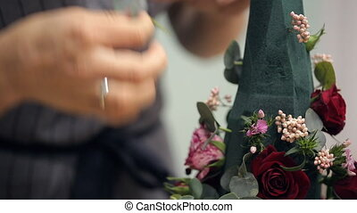 Florist inserts branch into cone-shaped basis of bouquet.