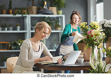 Florist leading small business, sitting beside desk, using...