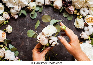 Florist makes a bouquet, top view with hands