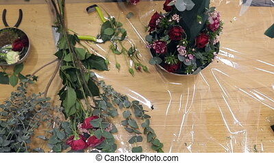 Florist makes a conical shape fresh flower arrangement in floral foam