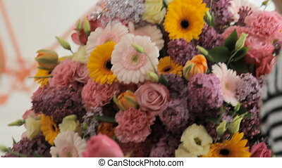 Florist makes a huge beautiful multicolored bouquet consisting of different flowers