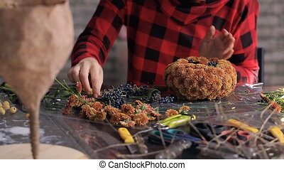 Florist makes composition of flowers, berries on wooden table.