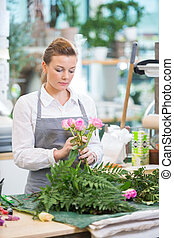 Florist Making Bouquet Of Roses In Flower Shop