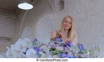 Florist making large floral basket with flowers at flower shop