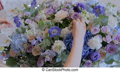 Florist making large floral basket with flowers at flower...