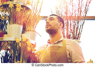 florist man with narcissus flowers at flower shop