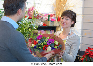 Florist passing bouquet of flowers to customer