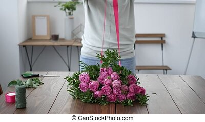 Florist prepares a bouquet of flowers for sale. Closeup...