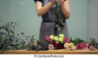 Florist prepares cut fresh flowers for a mixed bouquet arranging.