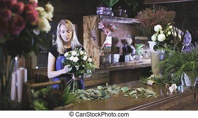 Florist preparing a flower bouquet in floral shop