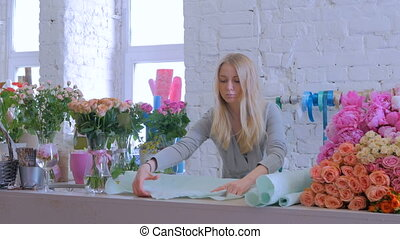 Florist preparing paper for bouquet at flower shop