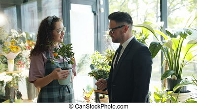 Florist pretty girl selling exotic plant to middle-aged man...