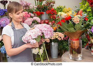New floral wonder. Young smiling florist holds flowers making a new floral arrangement