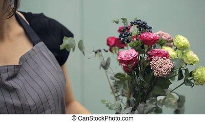 Florist recruit bunch of flower to create composition inside