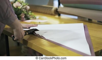 Florist s hands cutting wrapping paper on her table