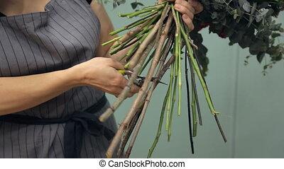 Florist scissors cuts long flower stems holds bouquet in office