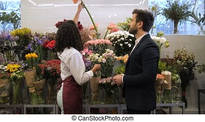 Florist selecting flowers for bouquet with client - Side...