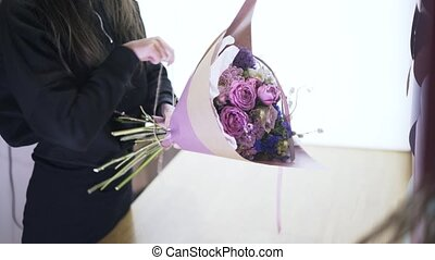Florist shop assistant tying a bunch of flowers in purple wrapping paper