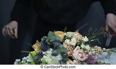 Florist shop assistant tying a bunch of flowers on a counter, cutting a thread