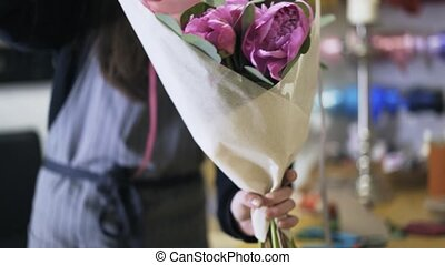 Florist shop employee wrapping a bunch of purple flowers