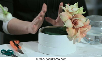 Florist show a flower arrangement in the round form white...